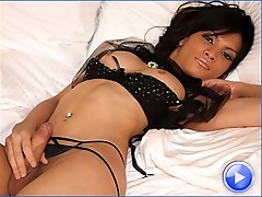 Slim latin shemale strokes her uncut cock while fingering her ass